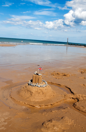 Union Jack in a sandcastle on a British beach