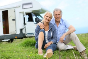 Happy senior couple sitting in grass, camper in background