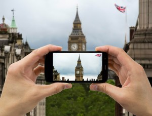 tourist holds up camera mobile at big ben with flag in london ** Note: Shallow depth of field