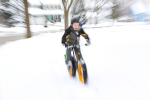 Boy riding a fat tire bike in winter snow. Motion blurred image.