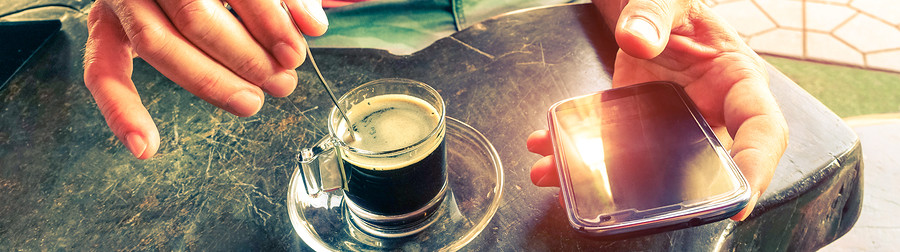 Man stirring coffee and holding smart phone at beach bar cafe restaurant - Hands with coffe cup and mobile top view on wooden table.