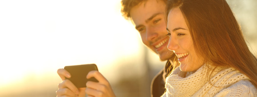 Happy couple watching media videos in a smart phone at sunset on the beach